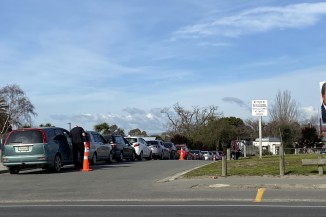 Line of cars at Covid-19 test site on Pages Road